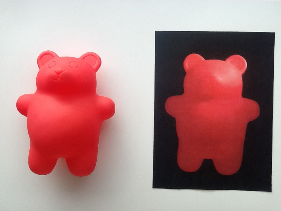 a red toy bear toy presented next to a photo of the exact same red toy bear